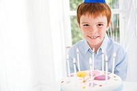 boy sitting at table with birthday cake