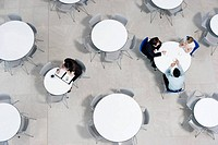 Overhead view of office workers at tables in the staff canteen