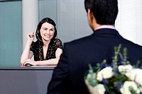 Businessman with bouquet of flowers being greeted by office receptionist