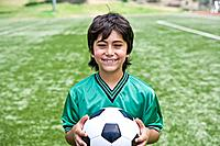 Smiling soccer player boy holding ball