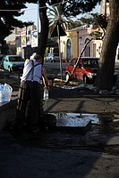 Man Filling Water Bottles from Standpipe in the Street Catania Sicily Italy