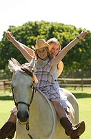 Two girls riding a horse