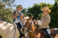 Two girls riding horses