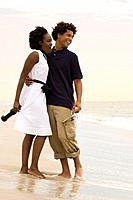 Couple with wine and glasses embracing at beach
