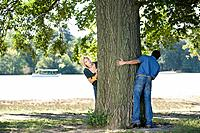 Playful couple at tree in park