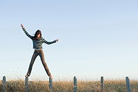 A woman balancing on fence posts