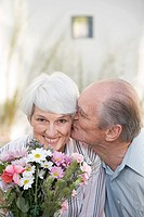 A senior man kissing a senior woman on the cheek