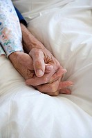 A senior couple holding hands
