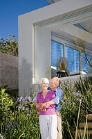 A senior couple stood in their garden
