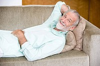A senior man reclining on a sofa