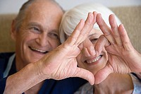 A couple making a heart shape with their hands