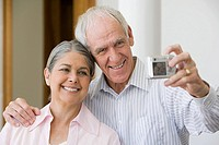 Senior couple with digital camera