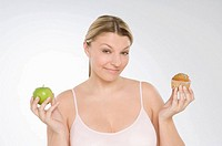 A woman deciding between a muffin and an apple