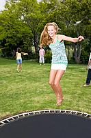 A teenage girl jumping on a trampoline