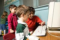A teacher showing her pupils how to use a computer
