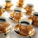 Golden cups of spiced coffee with spoons dipped in dark chocolate