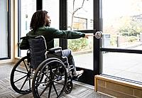 African man in wheelchair using automatic door (thumbnail)