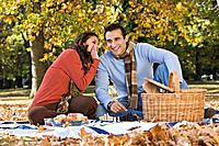 Hispanic couple telling secret at picnic