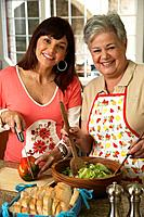 Hispanic mother and adult daughter preparing food