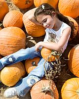 Hispanic girl laying in pumpkin patch
