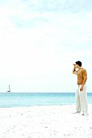 Man standing at the beach, looking at sailboat in the distance, side view