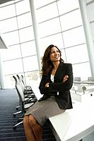 Hispanic businesswoman sitting on edge of table