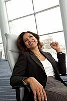 Hispanic businesswoman sitting in chair
