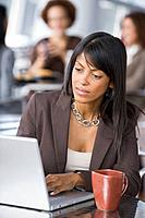 African businesswoman looking at laptop