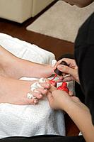 Asian spa technician painting toenails