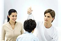 Young man and woman with boy, trying out head massager