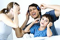 Family listening to CD player together, father and son using wireless headphones
