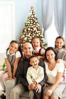 Hispanic family in front of Christmas tree