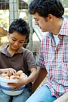 Multi_ethnic father and son with bowl of eggs