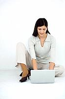 Woman sitting on the ground, using laptop computer, smiling