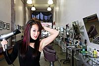 Asian hair stylist blow drying hair