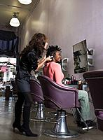 Hispanic hair stylist styling African woman's hair
