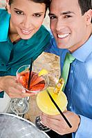 Hispanic couple toasting with cocktails