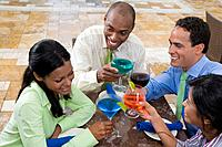 Hispanic couples toasting with cocktails