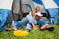 African couple reading at campsite