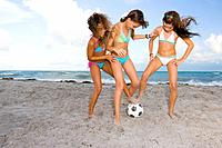 Multi_ethnic girls playing soccer at beach