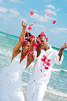Multi_ethnic couple throwing flower petals in air