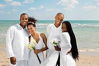 Multi_ethnic newlyweds hugging at beach