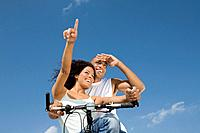 Multi_ethnic couple sitting on bicycle
