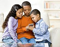 Mixed Race siblings looking at hand_held game