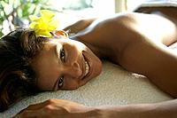 Hispanic woman laying on spa table