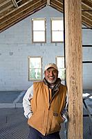 Hispanic man leaning on beam in new construction