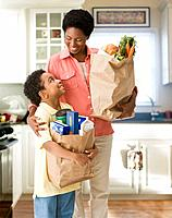 African mother and son holding bags of groceries