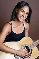 Mixed Race woman holding guitar