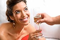 Hispanic woman accepting glass of champagne