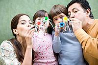 Hispanic family blowing noisemakers